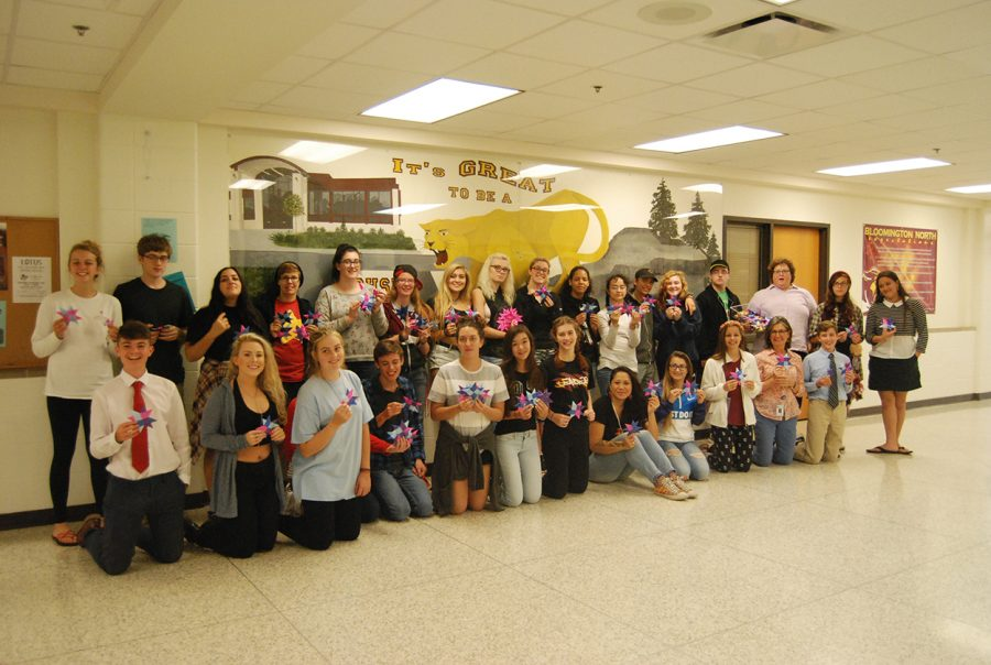 Students from the One Million Stars to End Violence tutorial take a break from weaving to pose for a group picture.
