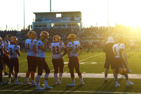 Members of the Cougar football team stand on the sidelines, awaiting play to resume